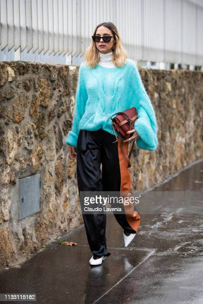 Candela Pelizza wearing a light blue sweater black and brown leather pants white heels and brown Loewe bag is seen outside Loewe on Day 5 Paris...
