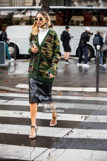 Candela Pelizza wearing a long military print cardigan and black leather midi skirt is seen outside the Miu Miu show during Paris Fashion Week...