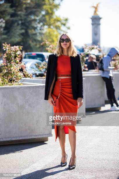 Candela Pelizza wearing a red Paco Rabanne top with matching midi skirt black blazer and black heels is seen after the Paco Rabanne show on September...