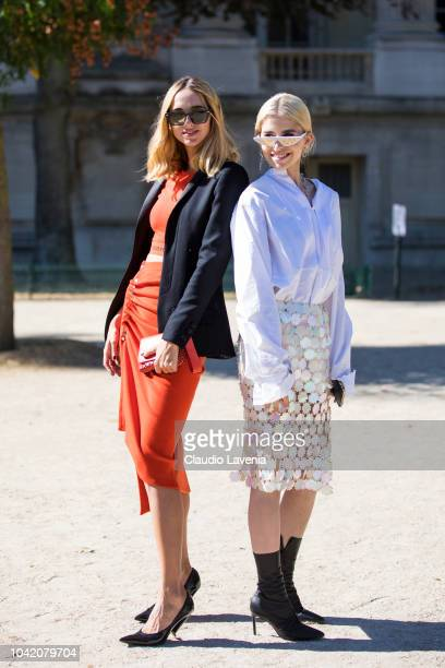 Candela Pelizza wearing a red Paco Rabanne top with matching midi skirt black blazer and black heels and Caroline Daur wearing a white shirt sequin...