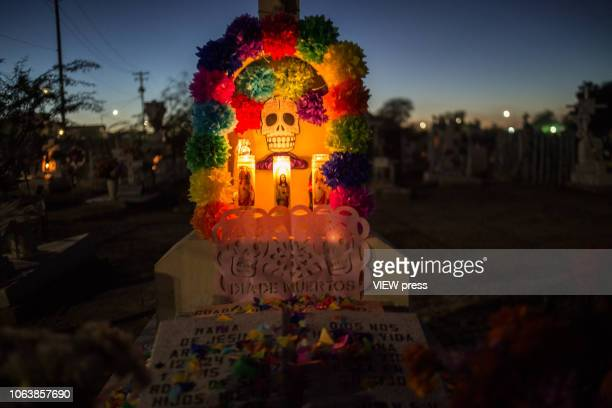 Candels are placed over a grave on the Municipal Cemetery on November 2 2018 in Mexicali Mexico Day of the Dead known asDía de Muertos is celebrated...