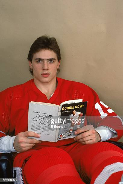 Candian professional hockey Steve Yzerman center for the Detroit Red Wings poses holding an open book about Canadian hockey player Gordie Howe...