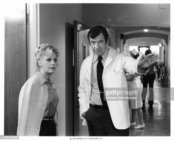 Candice Azzara and Walter Matthau talking in the hallway of a hospital in a scene from the film 'House Calls' 1978