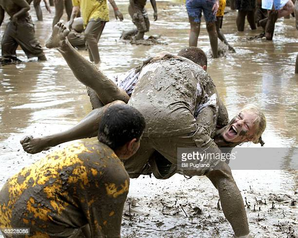 Candice Cook 19yearsold of Waterford Michigan gets tossed into the mud by Mike Benci 28yearsold of Waterford during the annual Mud Day event July 12...