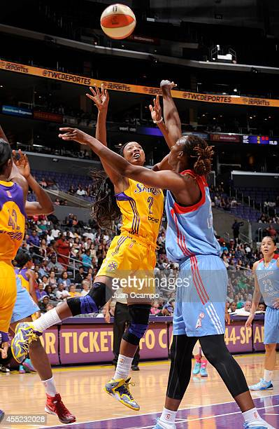 Candice Wiggins of the Los Angeles Sparks shoots over Sancho Lyttle of the Atlanta Dream at Staples Center on August 8 2014 in Los Angeles California...