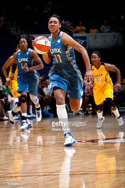 Candice Wiggins of the Minnesota Lynx charges downcourt on a breakaway leaving Ivory Latta of the Tulsa Shock behind during the WNBA game on June 30...