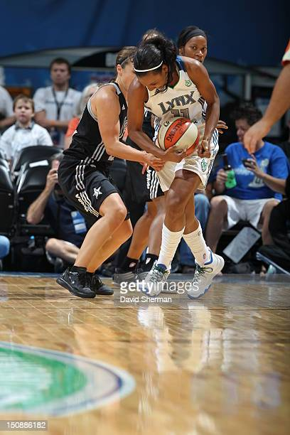 Candice Wiggins of the Minnesota Lynx protects the ball against Becky Hammon of the San Antonio Silver Stars during the WNBA game on August 28 2012...