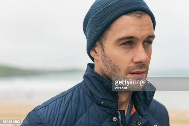 Candid beach Portrait of a handsome man wearing beanie hat.