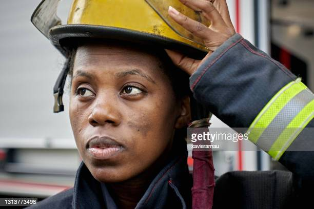 candid close-up of black female firefighter and helmet - firefighter stock pictures, royalty-free photos & images
