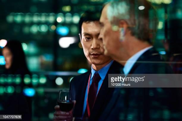 candid cropped portrait of two businessmen at evening event - celebratory event photos et images de collection