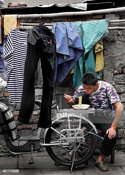 CONTENT] candid documentary style picture of a Chinese man eating a bowl of noodles from the carrier of his moped taken down one of the small lanes...