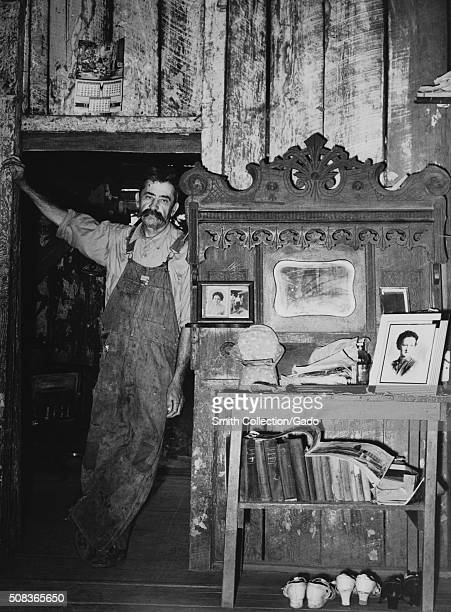 A candid full length portrait of a farmer leaning in a doorway inside of his house featuring family photographs a small collection of books and...