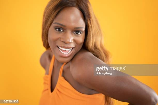 candid headshot of young black woman in orange halter top - halter neck stock pictures, royalty-free photos & images