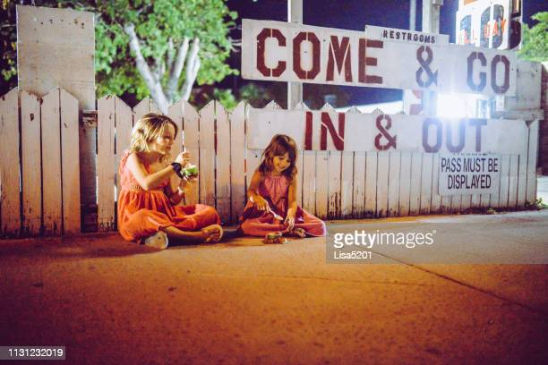 candid kids eating ice cream outside a parking lot on a hot summer night - hot dirty girl stock photos and pictures