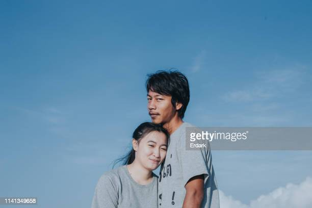 candid of thai couple enjoy travel beside cloudy sky with positive emotion on holiday - medium shot stock pictures, royalty-free photos & images