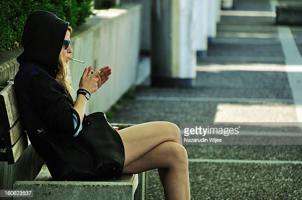 Candid photo of a lady lighting up her cigarette.