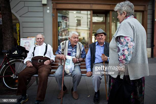 CONTENT] Candid photo taken spontaneously representing three old men talking to each other on a bench in Sibiu city Romania a standing woman seems to...