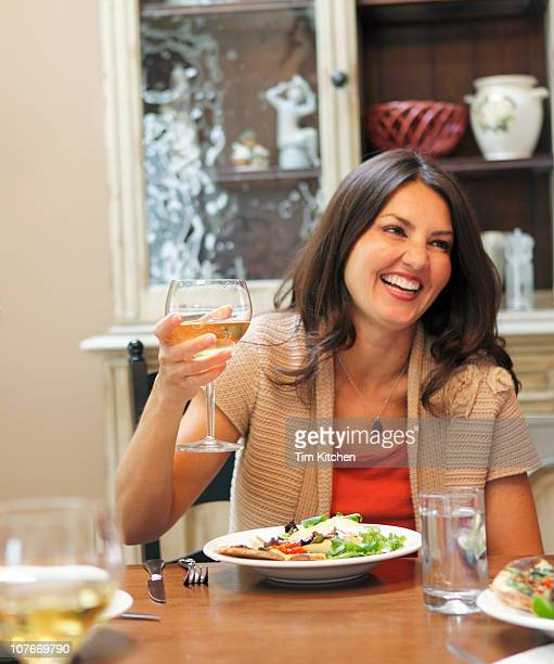 Candid picture of woman with wine glass and meal