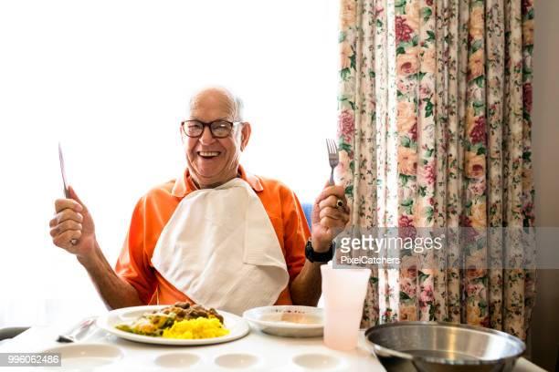 彼の 90ties は彼のナイフとフォークを保持してランチを食べて準備ができて、幸せな年配の男性の率直な肖像画 - テーブルナプキン ストックフォトと画像