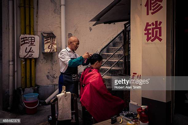 Candid portrait of a street barber cutting hair in a small corner of the street down one of the lanes of Shanghai
