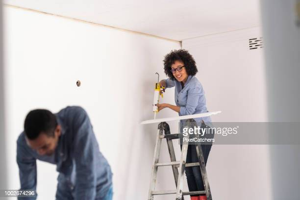 candid portrait of a young woman putting up cornice looking to camera - architectural cornice stock photos and pictures
