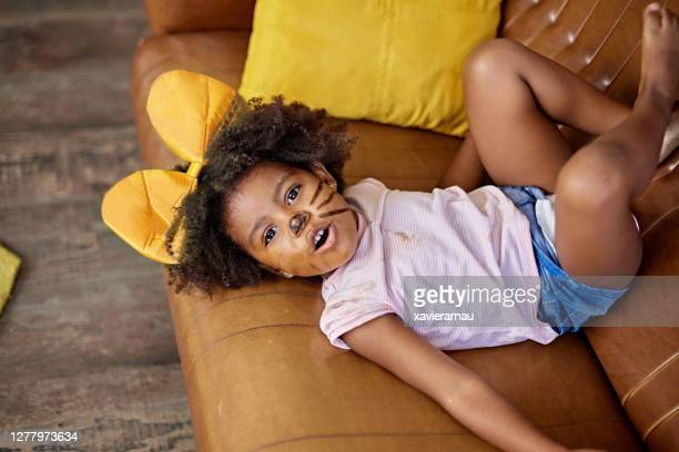 candid portrait of afro-caribbean child in costume headband - two seater sofa stock pictures, royalty-free photos & images