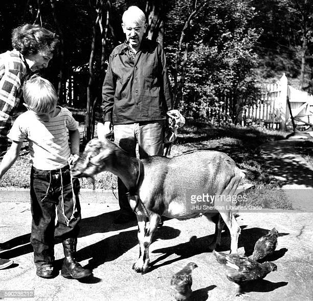 Candid portrait of American philosopher psychologist and educational reformer John Dewey standing on a path outside feeding a goat with his wife and...
