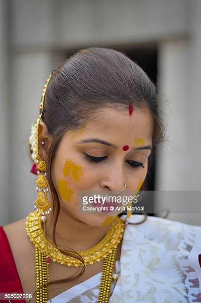Candid portrait of an Indian woman with gold jewellery and Turmeric also called Haldi