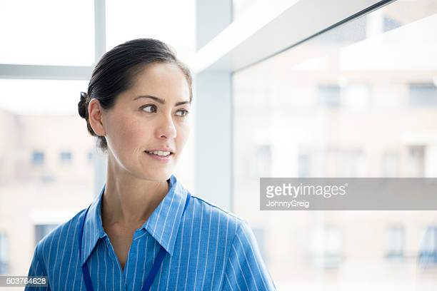 Candid portrait of Asian nurse looking through window