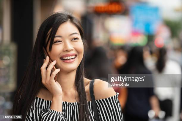 candid portrait of asian woman using mobile phone - off shoulder stock pictures, royalty-free photos & images