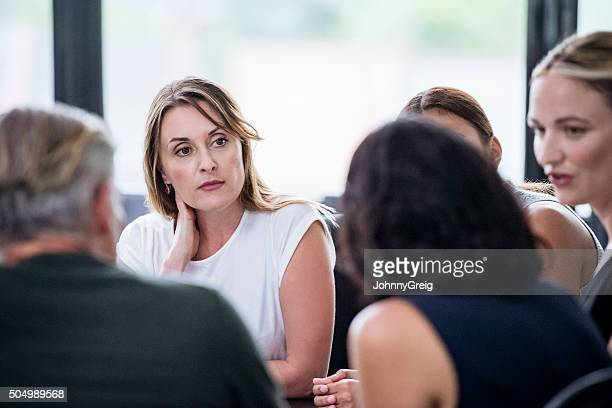 Candid portrait of businesswoman in meeting with group of colleagues