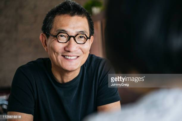 candid portrait of chinese man wearing glasses smiling - chinese ethnicity stock pictures, royalty-free photos & images