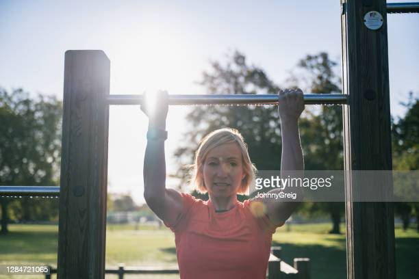 candid portrait of early 50s female athlete doing chin-ups - clapham common stock pictures, royalty-free photos & images