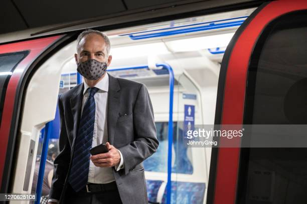 candid portrait of executive exiting train wearing face mask - station stock pictures, royalty-free photos & images