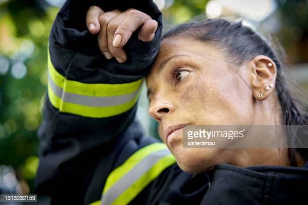 疲れ果てたヒスパニック系女性消防士の率直な肖像画 - すす ストックフォトと画像