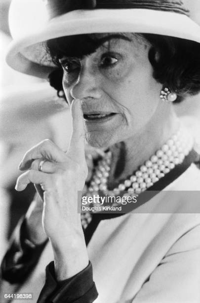 Candid portrait of fashion designer Coco Chanel touching her nose