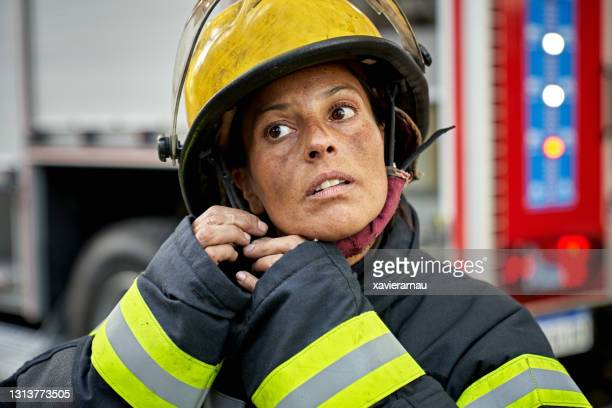 candid portrait of female firefighter putting on helmet - firefighter stock pictures, royalty-free photos & images