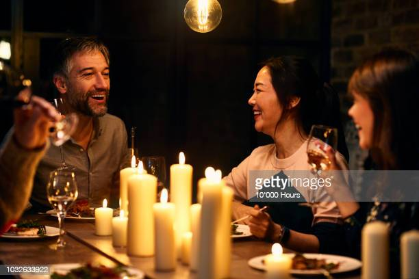 Candid portrait of friends chatting over dinner with wine