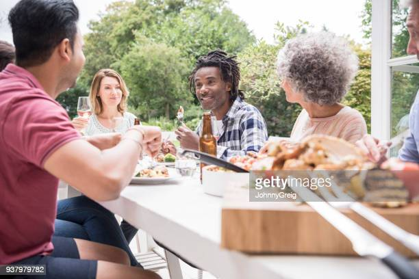 Candid portrait of friends eating lunch outdoors around table
