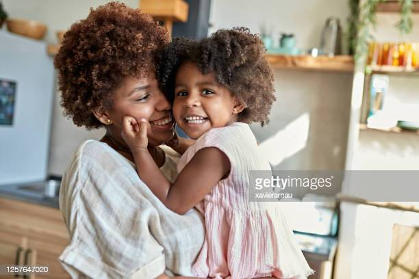 candid portrait of happy afro-caribbean mother and daughter - afro caribbean ethnicity stock pictures, royalty-free photos & images