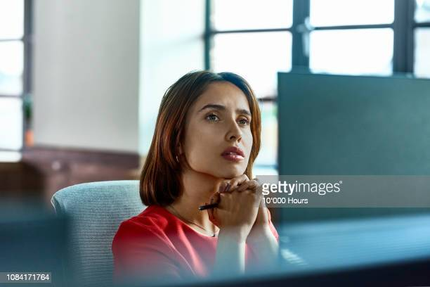 candid portrait of hispanic businesswoman deep in thought at desk - contemplation stock pictures, royalty-free photos & images