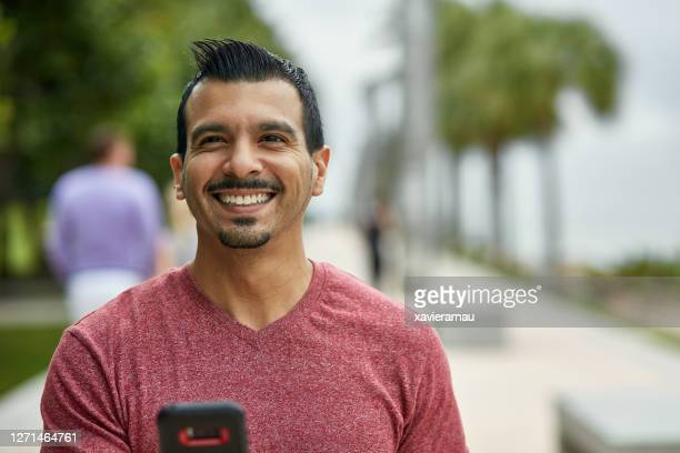 candid portrait of hispanic man reading good news on phone - v neck stock pictures, royalty-free photos & images