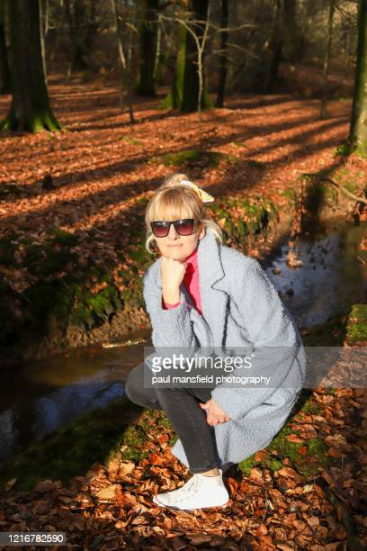 candid portrait of mature blond lady in forest - coat stock pictures, royalty-free photos & images