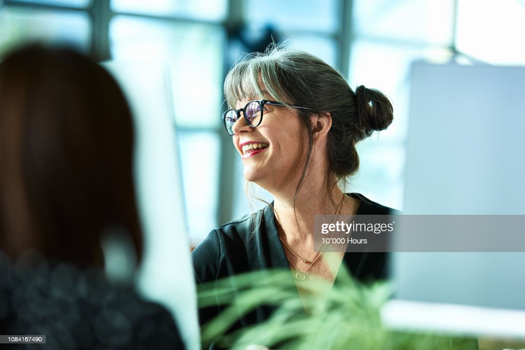 Candid portrait of mature businesswoman in glasses laughing : Stock Photo