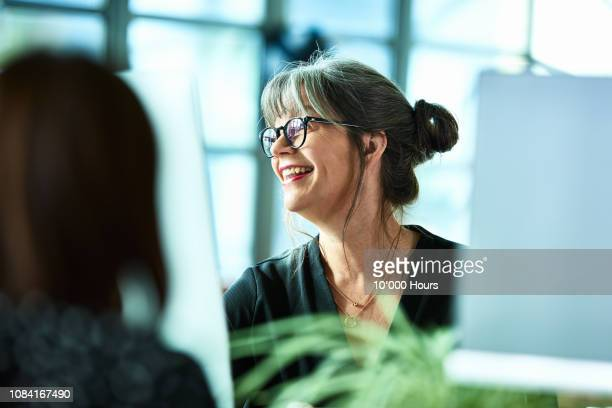 candid portrait of mature businesswoman in glasses laughing - trabajo de oficina fotografías e imágenes de stock