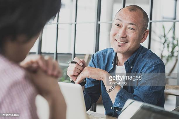 Candid portrait of mature Japanese man at work meeting