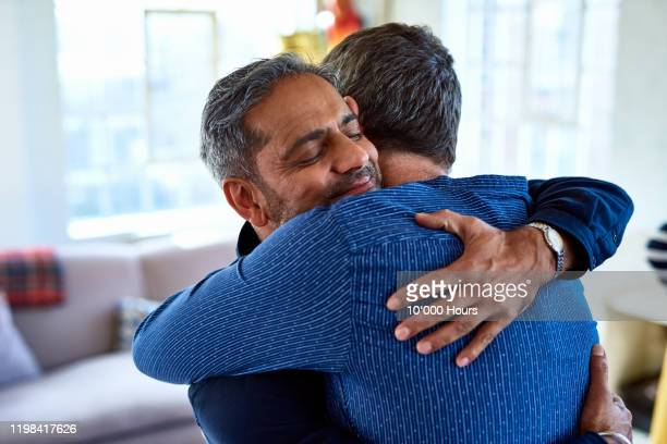 candid portrait of mature male friends hugging - happiness stock pictures, royalty-free photos & images