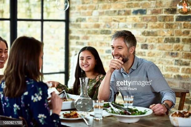 Candid portrait of mature man smiling at dinner party