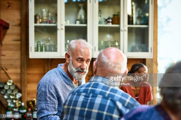 candid portrait of mature man talking to friend over dinner - balding stock pictures, royalty-free photos & images
