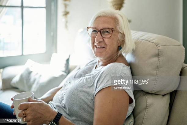 candid portrait of mature woman enjoying coffee at home - mid length hair stock pictures, royalty-free photos & images